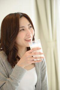 牛乳の入ったグラスを手にもつ女性の画像